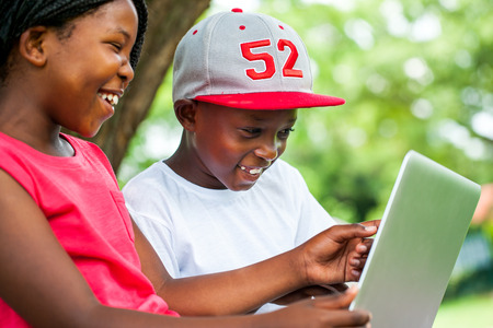 Close up portrait of African youngsters enjoying time with laptop in park. photo