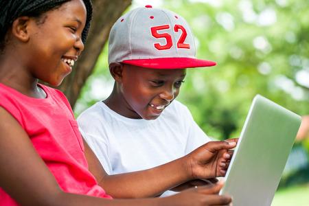 Close-up portret van Afrikaanse jongeren genieten van de tijd met de laptop in het park.
