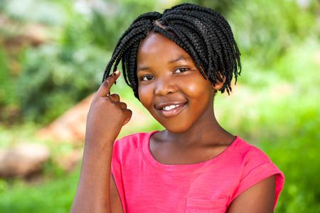 trenzas en el cabello: Close up retrato de la ni�a africana linda que muestra el pelo trenzado al aire libre en el parque.