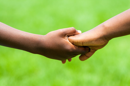 Extreme close up detail of African kids holding hands against green outdoor background.