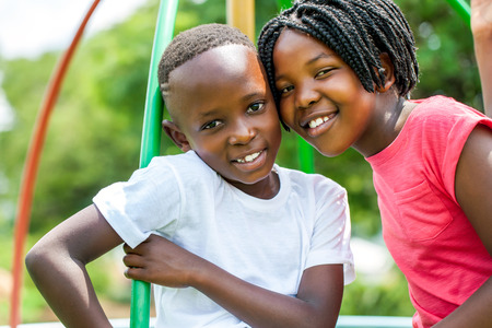 Close up face shot portrait of African kids joining heads in park.