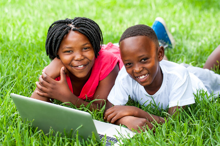 Close up portrait of cute African kids laying on grass with laptop.