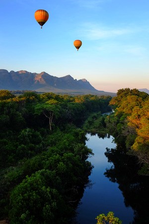 africa: Vertical image of two hot air balloons flying over African landscape with reflection on river.