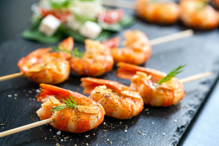 food buffet: Extreme close up of appetizing grilled queen prawn tail brochettes. Stock Photo