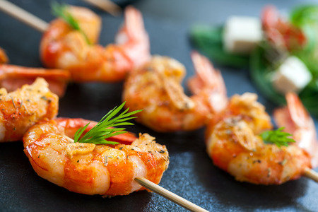 international food: Extreme close up detail of appetizing queen prawn brochette.