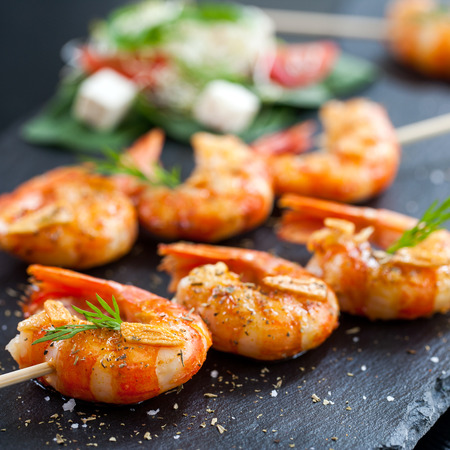 Macro close up of giant aromatic prawn tails spiced with natural herbs and grilled on wood skewer.