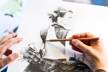 extreme close up: Extreme close up of female hands making fashion sketch.
