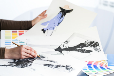 extreme close up: Extreme close up of fashion designer at work with fashion sketches and color charts.