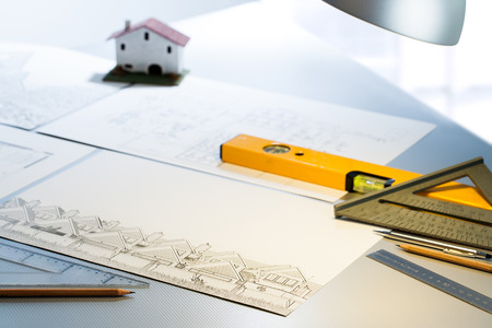 quantity surveyor: Detail of architect desk with technical drawings and measuring tools.