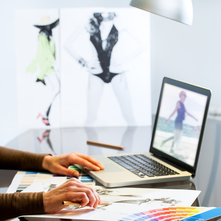 extreme close up: Extreme close up of Fashion Designers hands creating new collection on paper and laptop. Stock Photo