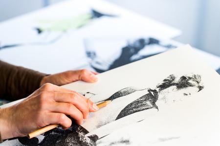 패션 스케치를 만드는 여성 패션 디자이너의 손의 극단적 인 닫습니다.