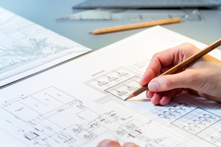 Macro close up of quantity surveyors hand reviewing technical drawing. Foto de archivo