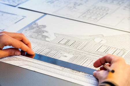 surveyor: Macro cerca de las manos de medición detalles sobre plan de la casa.