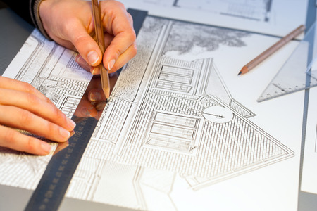 quantity surveyor: Extreme close up of human hands working on house plan project with pen and ruler.