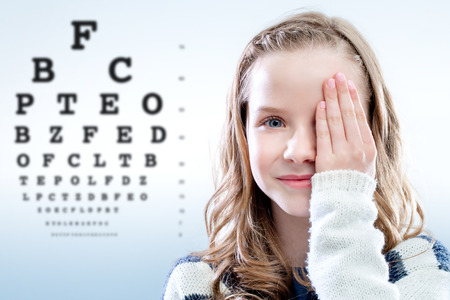 handout: Close up portrait of girl reviewing eyesight closing eye with hand.Out of focus test chart in background.