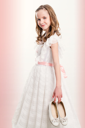 Close up portrait of cute Communion girl holding shoes.