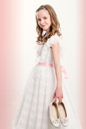 Nahaufnahme Porträt von niedlichen Mädchen mit Kommunion Schuhe.