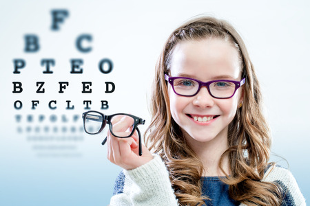 Close up portrait of young girl holding glasses with test chart in background.