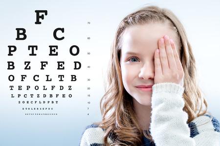 vision test: Close up retrato de la muchacha revisar ojo ojo cierre vista con la carta hand.Test en segundo plano. Foto de archivo