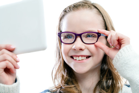 Close up portrait of Girl looking in mirror trying new glasses.Isolated on white background.