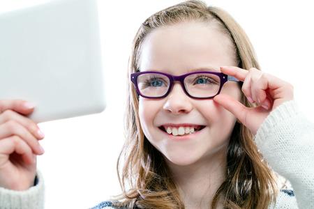 Close-up portret van meisje dat in spiegel kijkt proberen nieuwe glasses.Isolated op een witte achtergrond.