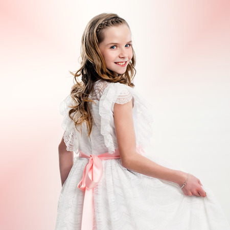 Close up studio portrait of cute girl in communion dress.