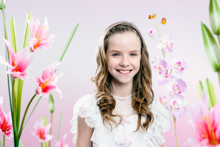 queen of angels: Close up portrait of young girl wearing communion dress in flower garden.