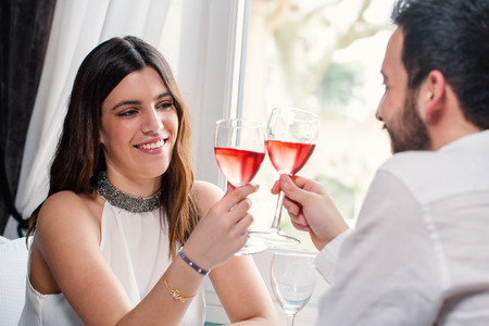 wine and dine: Close up portrait of attractive elegant brunette making a toast with red wine at dinner with boyfriend. Stock Photo
