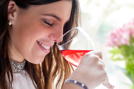 face shot: Close up face shot of attractive brunette smelling wine with eyes closed. Stock Photo
