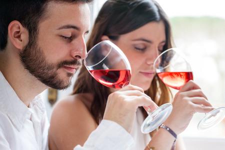 Close up portrait d'un jeune couple à la dégustation de vins. L'homme et la femme sentant vin avec les yeux fermés.
