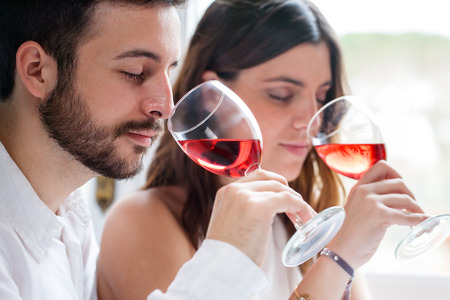 Close up portrait of young couple at wine tasting. Man and woman smelling wine with eyes closed.