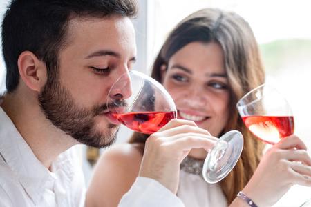 Close up portrait de couple, apprécier, et boire du vin à la dégustation.