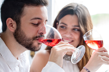 jovenes tomando alcohol: Close up retrato de Pareja disfrutando y bebiendo vino en la cata.
