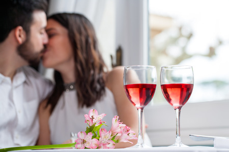 women kissing: Close up detail of two wineglasses with couple in background kissing. Wine glasses filled with rose wine next to flower bouquet. Stock Photo