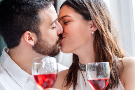 romantic kiss: Close up face shot of couple kissing at romantic dinner. Out of focus wine glasses in foreground. Stock Photo
