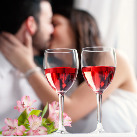 wine and dine: Close up of two wineglasses with rose wine and flower bouquet.In background a out of focus couple kissing. Stock Photo
