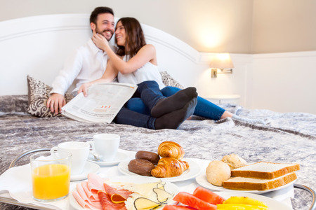 hotels: Close up detail of breakfast tray on bed with laughing young couple in background. Stock Photo