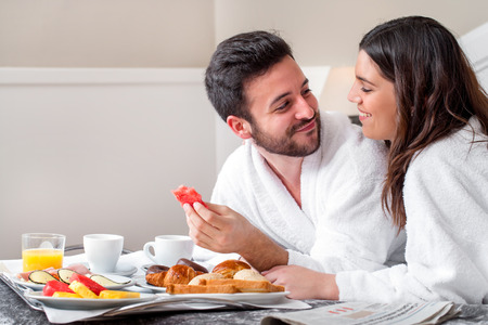 Close up portrait of young attractive couple enjoying breakfast in hotel room.
