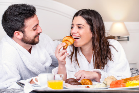 Close up portrait of couple having fun at breakfast in hotel room.Girl about to take bite of croissant. Banque d'images
