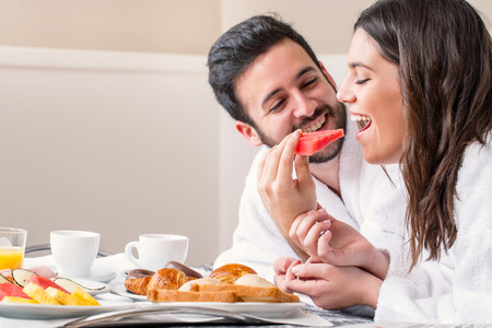 Close up fun portrait of couple in bathrobe on bed enjoying breakfast together.