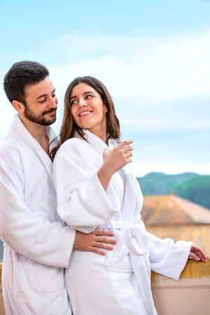 hotel balcony: Close up of young couple in bathrobe standing on hotel balcony against rural background.