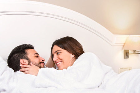romantic room: Close up portrait of cute young couple in bathrobe. Laying together on bed in hotel room. Girl showing affection. Stock Photo