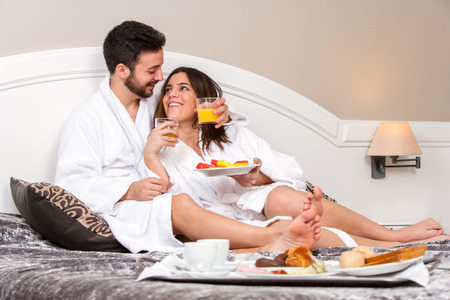 room service: Close up portrait of Young couple on honeymoon in hotel room. Couple enjoying room service with breakfast tray.