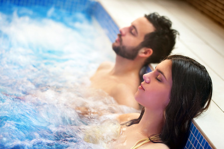 Close up portrait of young couple relaxing in spa jacuzzi. Couple together in bubble water with eyes closed. Banque d'images