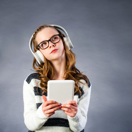 looking in corner: Close up portrait of Cute girl with head phones and digital tablet looking at corner. Girl wearing glasses with thinking face expression against dark background. Stock Photo