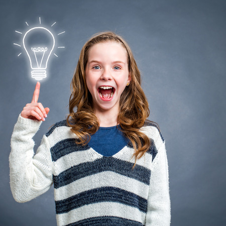 face expression: Conceptual portrait of cute surprised girl with shocking face expression pointing at light bulb against dark background.