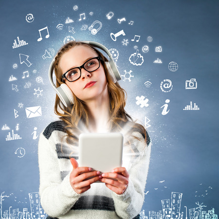bluetooth: Conceptual portrait of cute girl with glasses connected to internet with digital tablet. Girl wearing headphones with multiple signs and multimedia symbols floating against dark blue background.