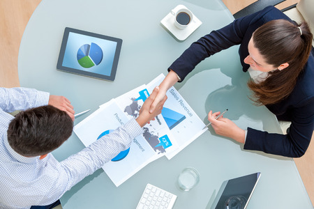 business table: Top view of young business partners shaking hands on deal at desk in office.Documents and digital tablet on table showing statistics and graphics.