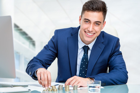 Close up portrait of young accountant counting money at desk. Young businessman in blue suit sitting at desk in office. Banque d'images