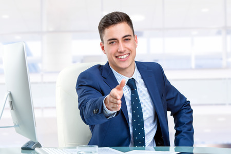 personal assistant: Close up portrait of Handsome businessman reaching out hand at desk. Young man in office in front of computer.
